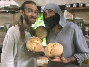 image shows permaculture teacher Anthony Bossler and Elton from paititi holding fresh sour dough breads from the clay oven